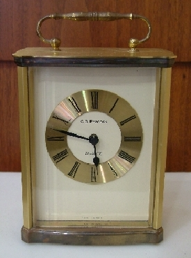C.D. Peacock brass clock w/handle. 4.5x3   base; 5   tall.