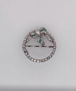 Platinum Art Deco Ribbon and Bow Circle Brooch with Diamonds and Emeralds Brooch Contains one Marquise Shaped Diamond weighing approximately 0.20CT J/VS1 58 early full cut damonds; approximately 1.8CTTW G-H/VS 8 Calibre Cut Emeralds
