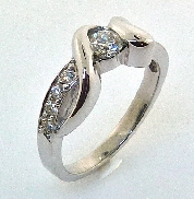 14KW Hearts On Fire engagement ring by Troy Shoppe Jewellers set with: - 0.234c Hearts On Fire diamond; I; VS2 HOF 154843 AGS#104089980023 - 8 Hearts On Fire diamonds; 0.153cttw; G/H; VS2-SI1