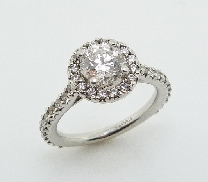 Platinum engagement ring Set in the center is one 0.786 carat F SI1 round brilliant cut diamond by Hearts On Fire. Claw set on the sides and halo are 38 round brilliant cut diamonds totalling 0.45 carats G/H SI-VS