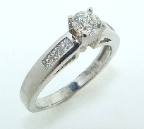 14K white gold engagement ring.          -Accented with princess cut diamonds; 0.24 carat total weight; VS-SI; G/H