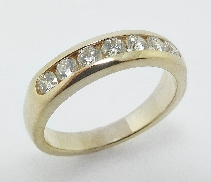 18K Yellow gold wedding band; known as   Duets Channel   by Hearts On Fire; (discontinued style) channel-set with seven I-J VS-SI ideal round brilliant cut diamons by Hearts On Fire; totaling 0.52 carats.