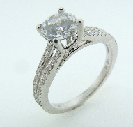 18K white gold engagement ring by Natalie K; set with 1.0 CZ. Accented with 50 G-H SI very good round brilliant cut diamonds totaling 0.26 carats.