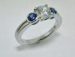 14 karat white gold diamond engagement ring by Frederic Sage set with: - 0.75 ct CZ  - 2 blue sapphires 0.40 cttw