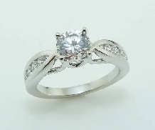 14KW engagement ring by Frederic Sage set with: - 0.75ct CZ  - 4 RBC; 0.11cttw; G/H; VS-SI - 12 RBC; 0.12cttw; G/H; VS-SI
