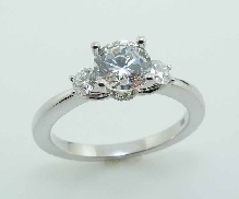 14KW diamond engagement ring by Frederic Sage set with: - 0.75ct CZ - 2 RBC diamonds; 0.20cttw; G/H; VS-SI - 10 RBC diamodns; 0.05cttw; G/H; VS-SI
