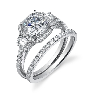 18K White gold engagement ring known as;   Vintage Round Brilliant Cushion Halo Diamond Engagement Ring  ; by Sylvie Collection Set with  -center 1.0ct round Cubic Zirconia  -accented with: 2 Baguettes 0.24 carats and round brilliant cut diamonds; 0