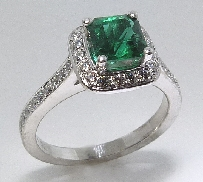 18 karat white gold coloured gemstone ring. Set with a 0.72 carat Radiant cut Emerald. Accented with 36 excellent cut diamonds; 0.26 carat total weight; SI; F/G.