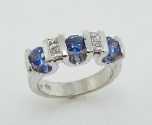 14 karat white gold coloured gemstone ring.  Set with 4 princess cut diamonds; 0.289 carat total weight; SI/VS; G/H. Accented with 3 blue sapphires; 0.866 carat total weight.