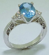 18 karat white gold coloured gemstone ring. Set with a 1.147 carat Aquamarine.  Accented with 14 round brilliant cut diamonds; 0.23 carat total weight; SI/VS.
