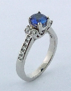 18 karat white gold coloured gemstone ring. Set with a 0.90 carat Blue Sapphire. Accented with diamonds; 0.42 carat total weight; SI+; H+.