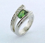 14K white gold colour gemstone ring by Studio Tzela Set with a 1.42 carat oval Green Zircon. Accented with round brilliant cut diamonds; 0.242 carat total weight; SI G/H
