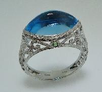 14 Karat white gold hand engraved ring set with: - 6.78 carat marquise cut; knife edge Swiss blue topaz  - 2 - 0.06 carat round; diamond cut tsavorites