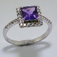 14 karat white gold gemstone ring. Set with one 1.25ct princess cut amethyst.  Accented with thirty I1/SI2 H/I round brilliant cut diamonds; totalling 0.24 carat.