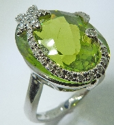 14 karat white gold coloured gemstone ring. Set with a 21.25 carat Peridot. Accented with 27 diamonds; 0.16 carat total weight.