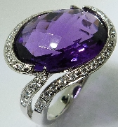 14K white gold ring; set with 8.10 carat oval checker cut purple amethyst. Accented with forty-one round brilliant cut diamonds; totaling 0.32 carat total weight.