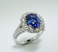 14 karat white gold coloured gemstone ring. Set with a 3.18 carat Oval Blue Sapphire. Accented with 12 diamonds; 1.10 carat total weight; SI1-SI2; G/H. Accented with 40 diamonds; 0.23 carat total weight.
