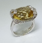 14 karat white gold ring. Set with one 10.50 caratretangular cushion cut Citrine. Accented with forty diamonds; totaling 0.20 carat total weight.