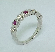 14K white gold coloured gemstone ring. Set with 3 princess cut rubies; 0.29 carat total weight. Accented with four round brilliant cut diamonds; 0.29 carat total weight; G-I SI1-I1.
