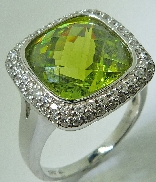 14 karat white gold coloured gemstone ring. Set with a 12.40 carat Peridot. Accented with 68 diamonds; 0.54 carat total weight.