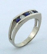 14 karat white gold coloured gemstone ring.  Set with 3 Blue Sapphires; 0.432 carat total weight. Accented with 2 round brilliant cut diamonds; 0.208 carat total weight; I1; I/J.