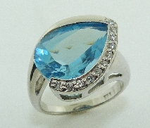14 karat white gold coloured gemstone ring. Set with a 9.7 carat Blue Topaz. Accented with 14 diamonds; 0.16 carat total weight; I; H/I.