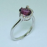 14 karat white gold coloured gemstone ring.  Set with one 1.72 carat Rhodolite Garnet. Accented with diamonds; 0.071 carat total weight.