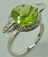 14 karat white gold coloured gemstone ring. Set with a 3.45 carat Peridot. Accented with 28 diamonds; 0.184 carat total weight; SI-VS; G/H.