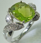 14 karat white gold coloured gemstone ring. Set with a 4.44 carat Cushion Cut Peridot. Accented with 39 diamonds; 0.249 carat total weight.