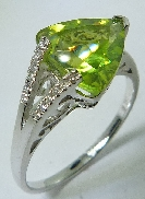 14 karat white gold coloured gemstone ring. Set with a 2.68 carat Triangular Peridot. Accented with 12 diamonds; 0.06 carat total weight.