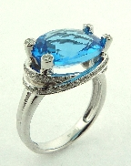 14 karat white gold coloured gemstone ring. Set with a 6.54 oval shaped Swiss Blue Topaz. Accented with 65 diamonds; 0.43 carat total weight.