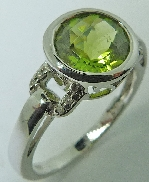 14 karat white gold coloured gemstone ring. Set with a 2.0 carat Peridot. Accented with 8 diamonds; 0.04 carat total weight.