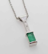 14 karat white gold coloured gemstone pendant by Studio Tzela. Set with a 0.59 carat Emerald. Accented with 2 round brilliant cut diamonds; 0.02 carat total weight; SI. Emerald Bar Pendant by Troy Shoppe Jewellers