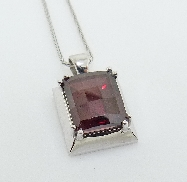 14 karat white gold coloured gemstone pendat.  Set with one 6.5 carat Cushion cut Rhodolite Garnet