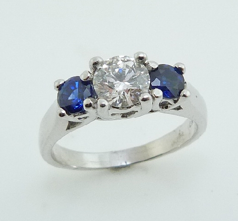 14K white gold three stone engagement ring; set with an ideal round brilliant cut diamond by Hearts On Fire -centre: 0.705ct F; VS1 (HOF60040) -accented with round faceted blue sapphires; 0.68 carat total weight