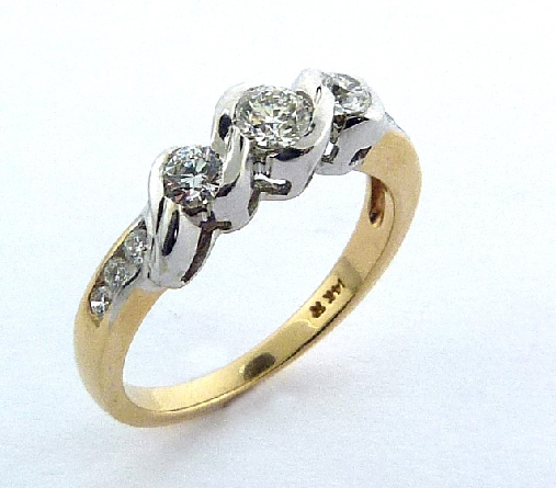 14K yellow and white gold engagement ring; set with an ideal round brilliant cut diamond by Hearts On Fire -centre: 0.244ct H; SI1 (HOF67295) -accented with ideal round brilliant cut diamonds by Hearts On Fire; 0.273 carat total weight; SI1-SI2; G