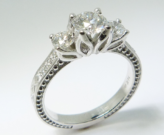 14K white gold floral detail engagement ring; set with an ideal round brilliant cut diamond by Hearts On Fire;  - -centre: 0.548ct H; VS1 (HOF111258) - -accented with ideal round brilliant cut diamonds by Hearts On Fire; 0.24ct H; VS2 (HOF127956) & 0.2