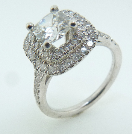 14 karat white gold engagement ring. Set with one 0.71 Fire Cushion; G; VVS; Cushion Brilliant Cut; GIA #1166054864 Accented with 0.57 carat total weight; SI; G/H.