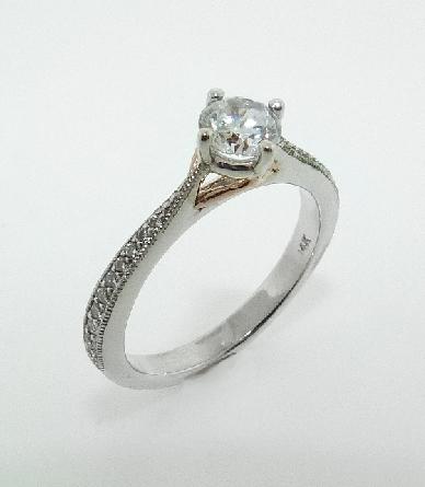 14KW diamond engagement ring set with:  - - 0.50ct CZ  - - 20 RBC diamonds; 0.14cttw; G/H; SI very good cut