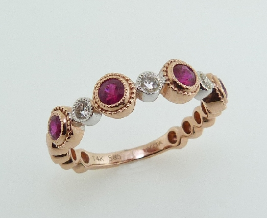 14K Two tone rose and white gold ladies band set with: 4 rubies totalling 0.48 carats 3 diamonds totalling 0.12 carats; SI1