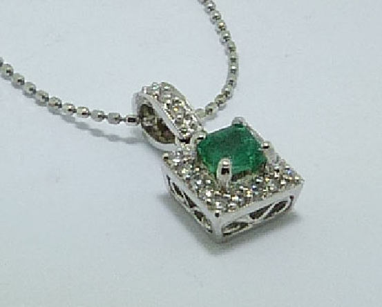 14 karat white gold coloured gemstone pendant by Natalie K. Set with a 0.27 carat Emerald. Accented with 20 round brilliant cut diamonds; 0.13 carat total weight.